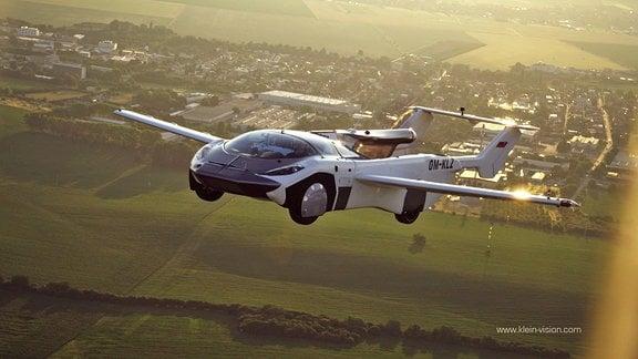 Ein fliegendes Auto über einer kleinen Stadt