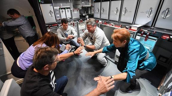 Eine Gruppe von Menschen macht an Bord eines Flugzeuges Kniebeuge o.ä., Ansicht von schräg oben