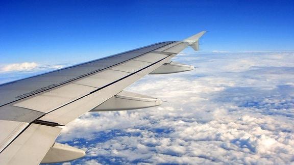 Flugzeuflügel vor blauem Himmel über der Erde und den Wolken, aus Flugzeugfenster gesehen.