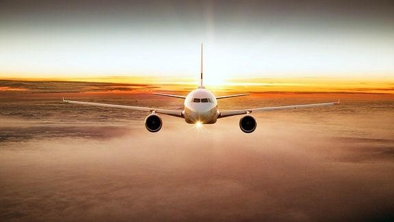 Fliegendes Flugzeug von vorn über den Wolken mit Sonnenuntergangsstimmung und rot-organge gefärbten Wolken im Hintergrund und darunter.