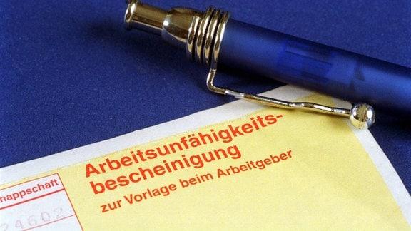 Arbeitsunfähigkeitsbescheinigung mit Kugelschreiber
