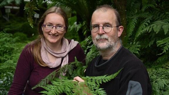 Frau mit langen Haaren, Brille und Schal sowie Mann mit kurzen Haaren, Brille und grauem Bart halten Farn-Wedel, im Hintergrund weitere Farne und Grünpflanzen wie im Wald.