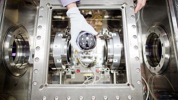 Ein PTB-Wissenschaftler hält in der Physikalisch-Technischen Bundesanstalt (PTB) in Braunschweig (Niedersachsen) eine exakt ein Kilogramm schwere Siliziumkugel vor einen Versuchsaufbau.