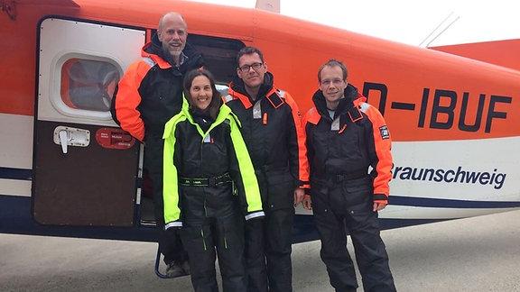 Drei Männer und eine Frau in Kälteschutzanzügen vor einem Flugzeug