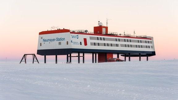 Die deutsche Antarktis-Forschungsstation Neumayer-Station III: Forschungsstation, die entfernt aussieht wie ein Schiff, mit roter, weißer und dunkelblauer/scharzer Farbgebiung auf Stelzen im Eis, Himmel wie in der Dämmerung leicht gelb-rosa gefärbt.