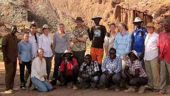 Vor steil aufragenden Felsen stehen und sitzen 17 Männer und Frauen