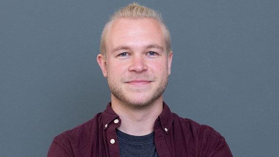 Junger Mann mit blonden Haaren und Drei-Tage-Bart lächelt mit geschlossenem Mund in die Kamera. Er trägt ein dunkelgraues T-Shirt und darüber ein weinrotes Hemd.