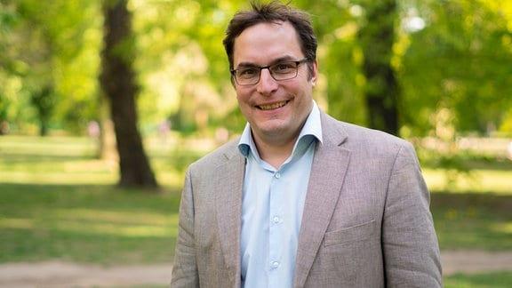 Mittelalter Mann mit Brille und kurzen dunklen Haaren lächelt, trägt ein hellblaues, offenes Hemd und ein graues Sakko und steht in einem Park.