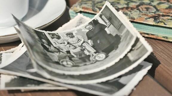 Alte Fotos liegen auf einem Tisch.