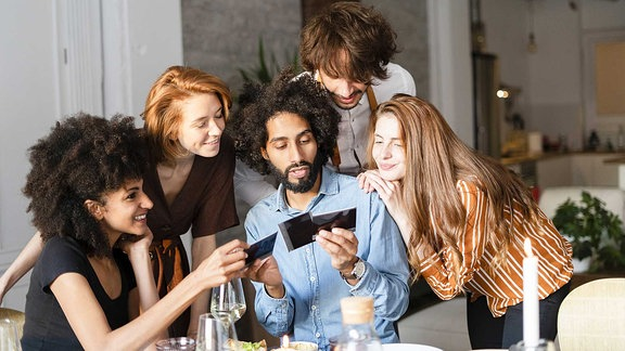Fünf Personen sitzen um einen Tisch herum und betrachten Fotos.