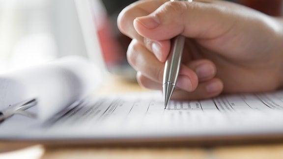 Hand mit Stift über Formular