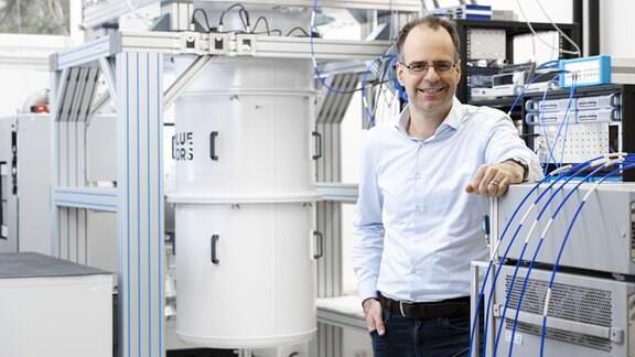 Ein mittelalter Mann mit Hemd und Brille steht in einem Labor neben einem weißen Großgerät aus Metall.