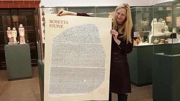 Dr. Franziska Naether mit Plakat des Rosetta-Steins im Ägyptischen Museum Leipzig