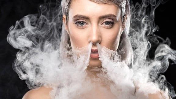 Eine junge Frau läßt den Dampf einer E-Zigarette durch die Nase raus