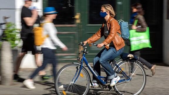 Fahrradfahrerin mit Mund-Nasen-Maske unterwegs im Berliner Stadtteil Prenzlauer Berg