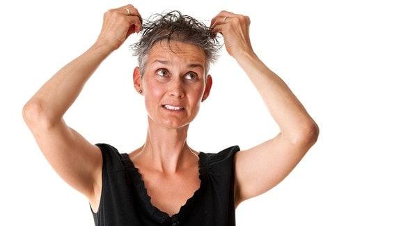 Frau rauft sich graue Haare