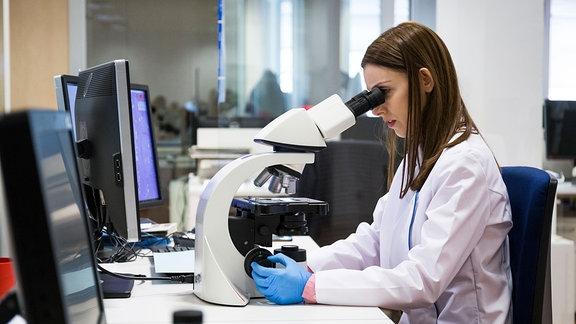Eine junge Frau sieht durch ein Mikroskop