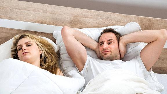 Ein Mann hält sich die Ohren zu während eine Frau neben ihm schläft