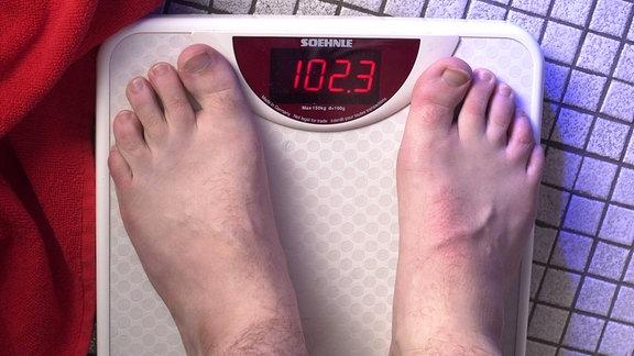 Füße auf Waage, diese zeigt 102,3 an