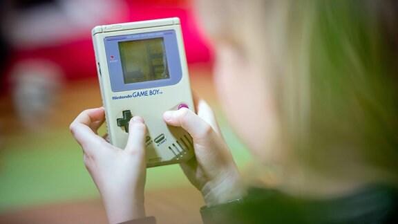 Kind spielt auf Gameboy der allerersten Generation das Spiel Tetis. Hintergrund farbig unscharf, Vordergrund unscharfer Kopf des Kinds, Blick über Schulter.