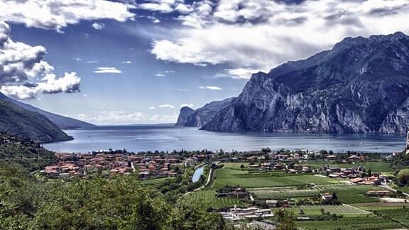 Der Gardasee, im Vordergrund grüne Felder und eine Ortschaft. Links flachere Berge zum Wasser abfallend, rechts höhere, steilere Berge mit Felsen.
