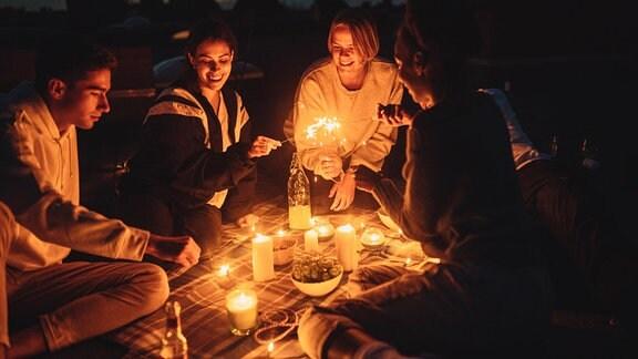 Freunde sitzen nachts auf einer Decke im Garten.Kerzen brennen.