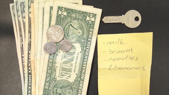 Geldscheine, Schlüssel, Visitenkarten und ein Notizzettel