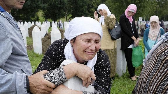 Trauernde Menschen auf einen Friedhof.