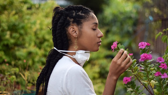 Junge Frau hat die FFP2-Maske abgenommen um an Blumen zu riechen