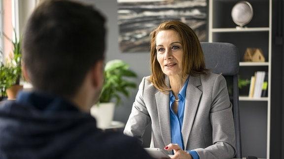 Szenario Bewerbungsgespräch an Schreibtisch. Eine Frau, mittig im Bild, frontal zu sehen, sitzt in einem Büro einer Person gegenüber. Person unscharf im Vordergrund, Blick über Schulter von hinten.
