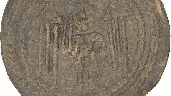 Münze des Münzherren Konrad Markgraf von Meißen, Prägedatum um 1150 – Darstellung der Grundfarbe: Auf der Münze sind noch wenige Reliefs auf grau-bräunlichem Grund zu erkennen.