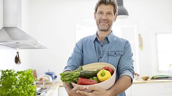Ein Mann mit einer Schüssel Gemüse im Arm, steht in einer Küche.