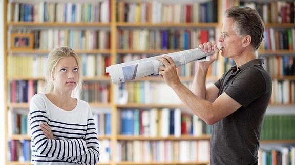 Vater schreit durch ein Megafon aus Zeitungspapier seine zwölfjaehrige Tochter an.
