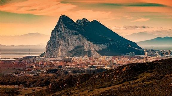 Abendstimmung mit warmen, orangefarbenen Licht: Blick auf Gibraltar – hoher Fels mit kleinem Städchten davor. Wolkenmuster und Berge im Hintergrund.