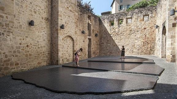 Touristen besichtigen den Gigantische Rosetta-Stein-Replik in Figeac.