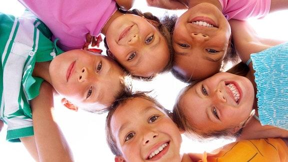 Fünf glückliche Kinder halten sich im Kreis an den Schultern fest.