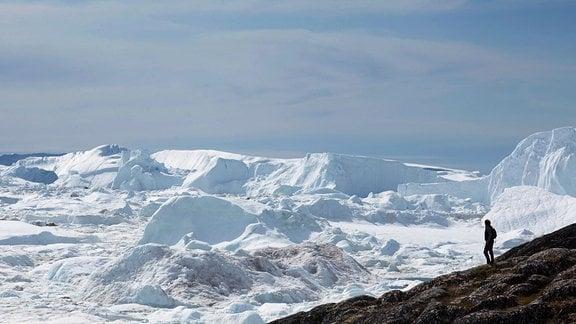 Symboldbild Gletscherschmelze: Person auf einer steinigen Schräge, darunter und dahinter endlos Gletscher mit Schmelzerscheinung