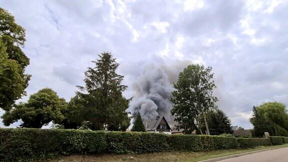 Riesige Rauchsäule über Häusern in Wohngebiet