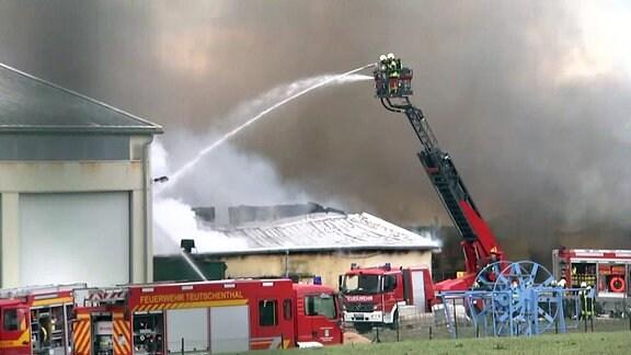 Feuerwehrleute löschen Brand und stehen auf Drehleiter in Rauch zwischen brennenden Ställen