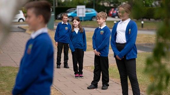 Britische Grundschüler in Schuluniformen stehen mit Abstand in einer Reihe
