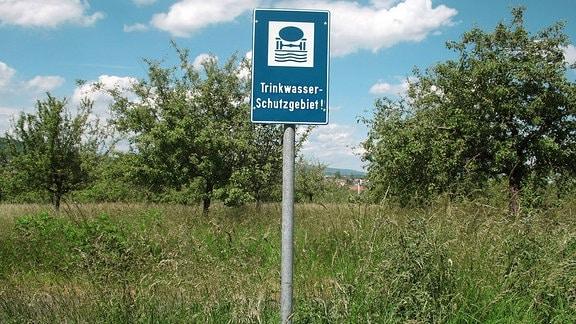 Ein Trinkwasserschutzgebietschild mit Büschen.