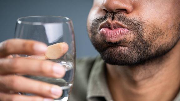 Mann hält Wasserglas und gurgelt.