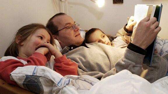 Vater liest seinen Kindern eine Gute-Nacht-Geschichte im Bett vor.