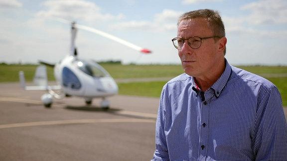 Mann mit Brille vor einem Gyrocopter