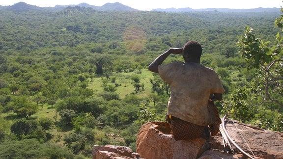 Mann sitzt auf einem Fels