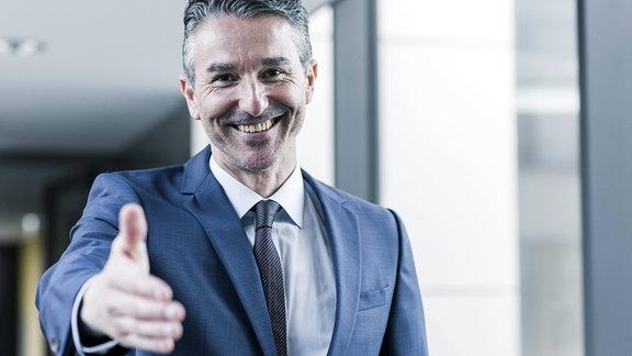 Porträt eines lächelnden Geschäftsmannes, der seine Hand ausstreckt.