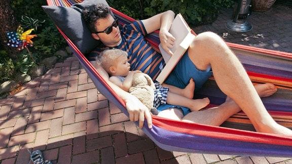 Vater und Sohn liegen lesend in einer Hängematte