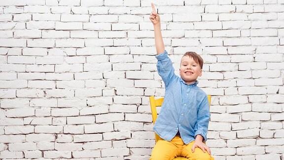 Ein Schüler mit blauem Hemd und gelber Hose sitzt auf einem Stuhl vor einer weißen Ziegelwand und meldet sich. Gestreckte Körperhaltung, Kopf nach oben gerichtet, freudiges Gesicht.