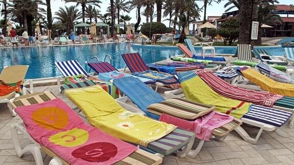 Sonnenliegen, an einem Pool, belegt mit Handtüchern.