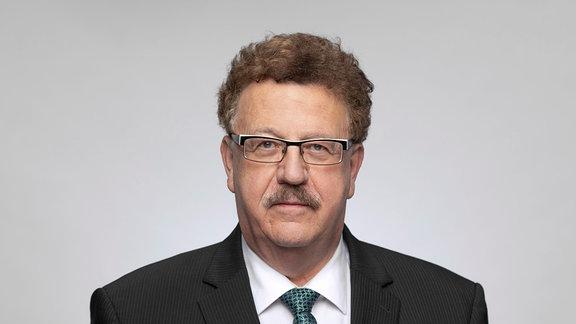 Porträt von Mann mit lockigen, kürzeren Haaren, Brille, Anzug und Oberlippenbart, blickt freundlich in Kamera